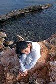 Femme pensive assisse sur des rochers côtiers