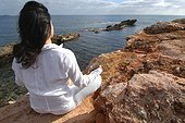 Femme méditant en position du lotus face à la mer