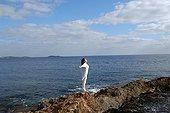 Femme s'étirant et respirant l'air de la mer