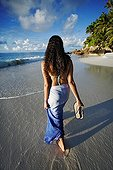 Woman walking on a tropical beach Frigate Island Seychelle ; Anse Victorin beach, voted by the London Sunday Times as the word's best beach. <br>@ Frigate (Island)