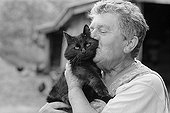 Woman kissing with tenderness a black cat