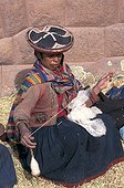 Woman in traditional clothe spinning wool Peru