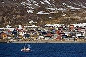 Petit chalutier passant devant un village côtier Norvège