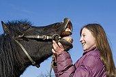 Adolescente avec son poney hennissant France