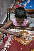 Child broded a brightly colored fabric over India