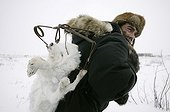 Hunter carrying on his back an Arctic Fox trapped in Canada
