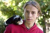 Adolescent portant un Cochon d'Inde sur son épaule