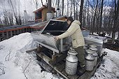 Man watching a storage tank of Maple water Quebec Canada ; Locality: St Mathieu du Lac.<br>Maple water is pumped into the aluminium tank by an electric pump and hoses which are directly connected to maples. Then the sap is boiled and will evaporate till just leaving the Maple syrup.