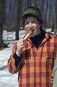 Boy eating a maple syrup sweet Quebec Canada ; Locality: St Mathieu du Lac. <br>The maple taffy - enjoyed on a wooden stick - is a highly prized delicacy in winter.