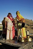 Women drawing water from a well India