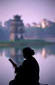 Old woman reading near water Hanoi Vietnam