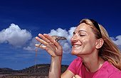 Blue whiptail lizard on the hand of a tourist Bonaire