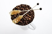 Sugar sticks lying on top of a cup filled with coffee beans