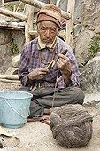 Man spinning wool Valley Lingti Zanskar India ; Farmer mountain wool putting on a distaff