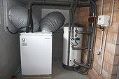Pompe à chaleur air-eau dans la maison d'un particulier ; Prises d'air dans le mur, ballon tampon et pompes de circulation