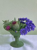 Bouquet of bull thistles and garden cornflowers in a vase