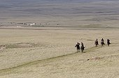 Horsemen trotting in pastures near lake Son Kul Kyrgyzstan ; In the background, yurts and cattle are visible.