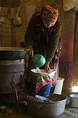 Young nomadic woman filtering milk in a yurt in Kyrgyzstan
