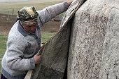 Grand-mère ajustant le feutre d'une yourte Kirghizistan