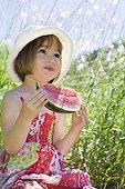 Petite fille de trois ans tenant un quartier de Pastèque