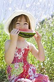 Petite fille de trois ans qui mange un quartier de Pastèque