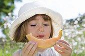 Petite fille de trois ans qui mange un quartier de Melon