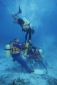 Divers performing underwater Red Sea Egypt ; Using a pneumatic drill pneumatic, divers percent a hole to plant an anchorage fixed to moor vessels of diving clubs. For this work, Marine Park of Ras Mohamed a completely forbidden for many years, anchor with an anchor. Protection of coral reefs