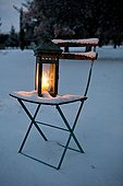 Lantern on a chair with snow in Provence