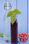 Raspberry syrup and bottle of water on a blue table France