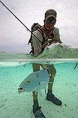flyfisherman with Bluefin Trevally in tropical lagoon, Indian Ocean Alphonse Island, Seychelles