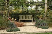 Pergola and bench The Garden of Marie-Ange Croisette ; Coneflower (yellow flower), Autumn Sedge, Everbrown sedge, Hydrangea, rose-tree and Dianthus