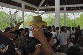parieurs lors de combats de Coqs Bali Indonésie ; Les combats de coqs, interdits en Indonésie, profitent d'une tolérance sur<br>l'île de Bali. Le combat (tetadjen ou sabungan) a lieu dans une arène carrée<br>de 6 mètres de coté, dans un programme composé de 9 ou 10 matches (sehet). Une<br>dizaine d'hommes pénètrent dans l'arène. Chacun portant un coq et recherchant<br>un adversaire idéal. On attache à chaque coq son éperon (tadji) de 10 à 12 cm.<br>Leur fixation requiert un savoir faire particulier, celui des éperonniers peu<br>nombreux. Les combats sont régis par des règles minutieuses et ancestrales. Une fois un coup décisif porté, les coqs sont séparés.