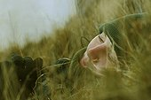 Warmly dressed young woman lying in the Grasses