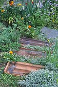 Old tiles made garden path in a garden