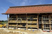 Pose des bottes de paille dans une maison à ossature bois ; Enduits naturels en terre basse énergie bioclimatique HQE. Maison des Vergers du Paysage et de l'Énergie