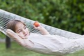 Girl lying in a hammock and taking a Apricot  ; Child is 4 years old