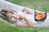 Girl lying in a hammock and eating an apricot ; Child is 4 years old
