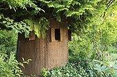 Shelter woven wicker around a Thuya Le Jardin des Lianes ; Le jardin des lianes