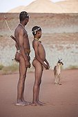 """Farther and son San with caracal n background Namibia ; In the private reserve named """"N/a'an ku sê"""", welfare programs and health support converge to maintain populations of Bushmen in good health and to reintroduce the wild Cheetahs. This nomadic group of hunter-gatherers has a history dating back over 20,000 years. Their close relationship and perfect their knowledge of animals allowed to live and feed in the deserts of southern Africa."""