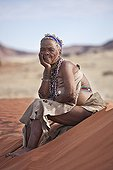 """Elderly woman San wearing traditional dress sitting on sand ; In the private reserve named """"N/a'an ku sê"""", welfare programs and health support converge to maintain populations of Bushmen in good health and to reintroduce the wild Cheetahs. This nomadic group of hunter-gatherers has a history dating back over 20,000 years. Their close relationship and perfect their knowledge of animals allowed to live and feed in the deserts of southern Africa."""