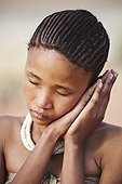 """Portrait of young San girl in the Namib desert Namibia ; In the private reserve named """"N/a'an ku sê"""", welfare programs and health support converge to maintain populations of Bushmen in good health and to reintroduce the wild Cheetahs. This nomadic group of hunter-gatherers has a history dating back over 20,000 years. Their close relationship and perfect their knowledge of animals allowed to live and feed in the deserts of southern Africa."""