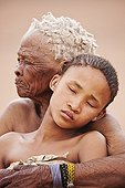 """Young San girl with old woman embracing in Namibia ; In the private reserve named """"N/a'an ku sê"""", welfare programs and health support converge to maintain populations of Bushmen in good health and to reintroduce the wild Cheetahs. This nomadic group of hunter-gatherers has a history dating back over 20,000 years. Their close relationship and perfect their knowledge of animals allowed to live and feed in the deserts of southern Africa."""