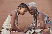 """Young San girl with old woman embracing Namibie ; In the private reserve named """"N/a'an ku sê"""", welfare programs and health support converge to maintain populations of Bushmen in good health and to reintroduce the wild Cheetahs. This nomadic group of hunter-gatherers has a history dating back over 20,000 years. Their close relationship and perfect their knowledge of animals allowed to live and feed in the deserts of southern Africa."""