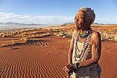 """Elderly San female standing in desert landscape Namibia ; In the private reserve named """"N/a'an ku sê"""", welfare programs and health support converge to maintain populations of Bushmen in good health and to reintroduce the wild Cheetahs. This nomadic group of hunter-gatherers has a history dating back over 20,000 years. Their close relationship and perfect their knowledge of animals allowed to live and feed in the deserts of southern Africa."""