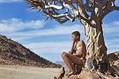 """Young San girl leaning against quiver tree Namibia ; In the private reserve named """"N/a'an ku sê"""", welfare programs and health support converge to maintain populations of Bushmen in good health and to reintroduce the wild Cheetahs. This nomadic group of hunter-gatherers has a history dating back over 20,000 years. Their close relationship and perfect their knowledge of animals allowed to live and feed in the deserts of southern Africa."""