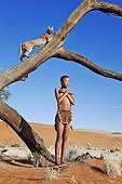 """Young San girl with Caracal on tree stump Namibia ; In the private reserve named """"N/a'an ku sê"""", welfare programs and health support converge to maintain populations of Bushmen in good health and to reintroduce the wild Cheetahs. This nomadic group of hunter-gatherers has a history dating back over 20,000 years. Their close relationship and perfect their knowledge of animals allowed to live and feed in the deserts of southern Africa."""