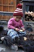 Child peeling a potato on the skin of Yack Chame Nepal