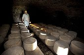 Cantal cheeses in the cellar of a buron France ; Traditional cheese. The building is buron traditional stone used for summer pastures.