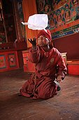 Young Buddhist monk playing with a packet Muktinath Nepal