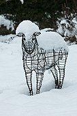 Sheep statue in a garden under snow